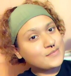 Photo of a young adult with curly hair, wearing a green headwrap and a nose ring.