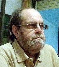 Photo of a balding middle-aged man with glasses, a collared shirt, and a serious expression.