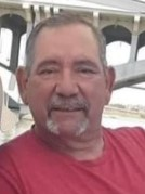 Photo of a middle-aged man with tanned skin and short gray hair and beard. He is wearing a red shirt.